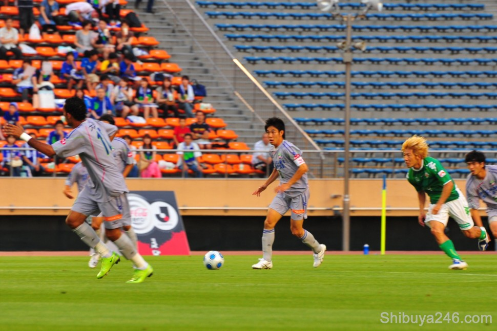 With the match underway, Tokushima Vortis in the gray strip make an attacking move