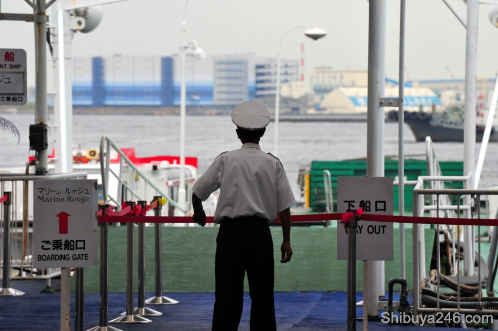 A crew member for the Marine Rouge tourist ship looks out onto the Yokohama Harbor
