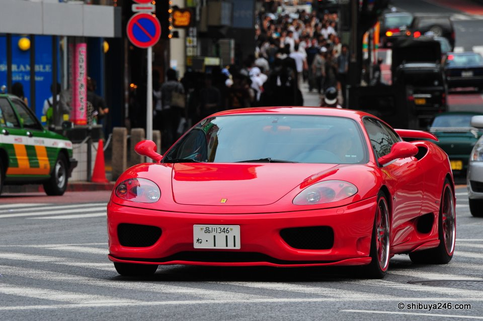 Red Ferrari rolls through the Shibuya Streets.