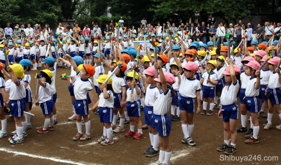 As the music starts and the 1964 Olympian runner enters, the kids hold their Torches high