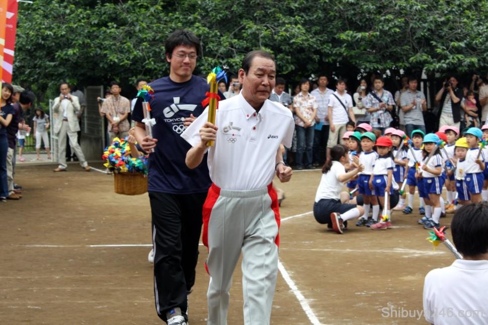 Yoshinori Sakai, the final torch bearer from the 1964 Tokyo Olympics leads the runners into the kindergarten