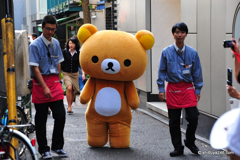Store attendants guide Rilakkuma down the backstreets towards the store