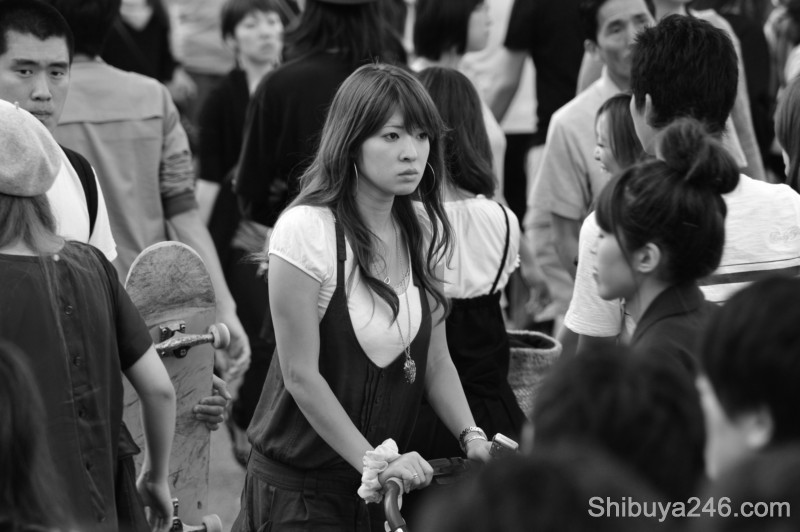 A mother takes a moment of reflection as she pushes her pram through the crowds. What type of fashion will her child claim for the next generation of Shibuya young