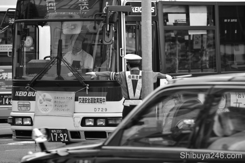 The bus is directed into its spot. Tokyo 2016 Olympic banners on the front