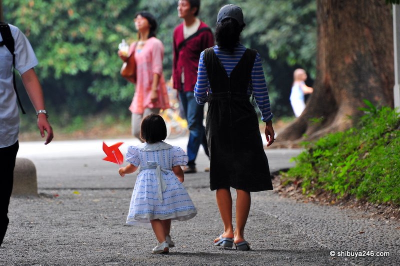 A mother and child walking down the gravel path. Lovely dress