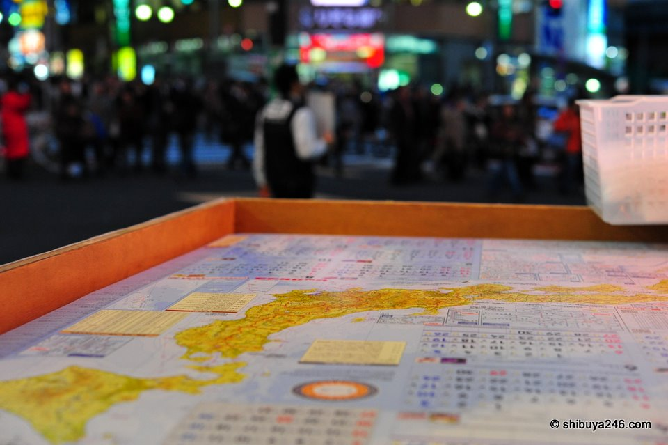 Heading into Bic Camera to look at some other digital cameras. Saw these free 2010 Japan map calendars out and decided to try a shot of them with a reflection of the crowd. Not quite what I was looking for, but interesting nonetheless (Nikkor 60mm)