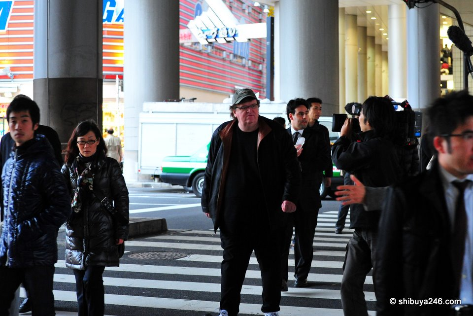 The NHK crew film as Michael Moore walks towards Shibuya Station