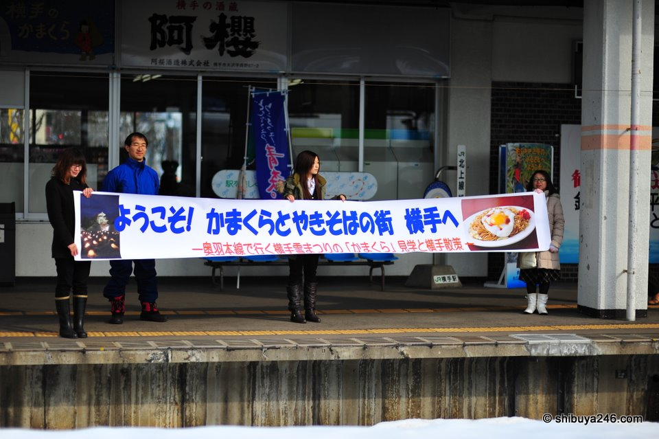 "The welcoming committee at the local Yokote train station. The sign says ""Welcome to Yokote, the town with kamakura and yakisoba"""