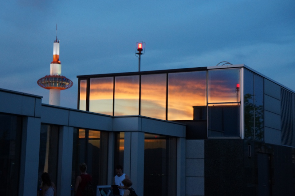A quick view of Kyoto Tower with sunset reflected from buildings